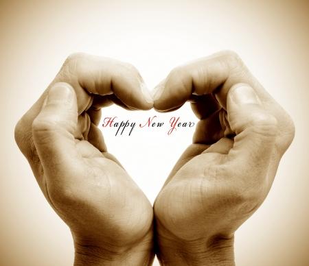 fin d annee: mains formant un coeur et la peine happy new year