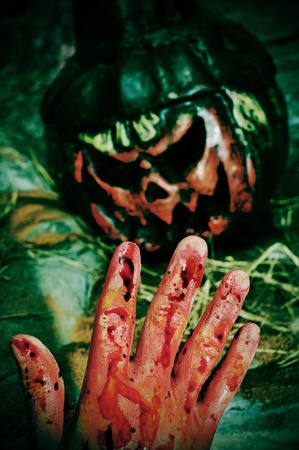 closeup of a bloody hand and a scary Halloween jack-o Stock Photo - 10729785