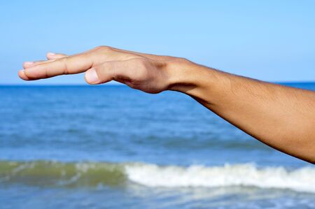 a man arm waving free in the air with the ocean at the background Stock Photo - 10729779