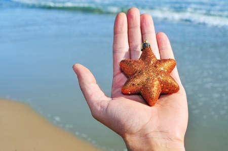 a golden christmas star on a hand on the beach Stock Photo - 10829243