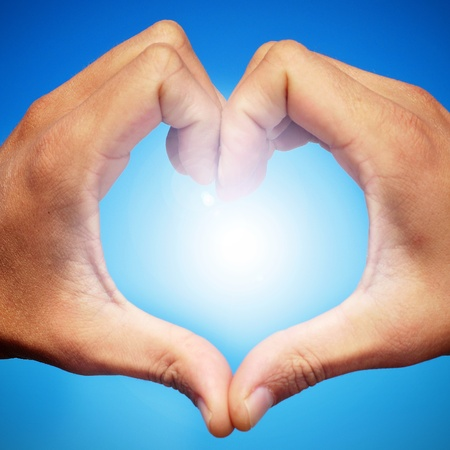 man hands forming a heart over the sky Stock Photo