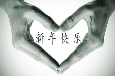 hand written: hands forming a heart and the sentence happy new year in chinese Stock Photo