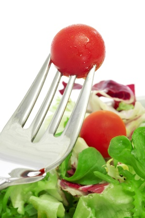 cornsalad: closeup of a plate of salad and a cherry tomato in a fork