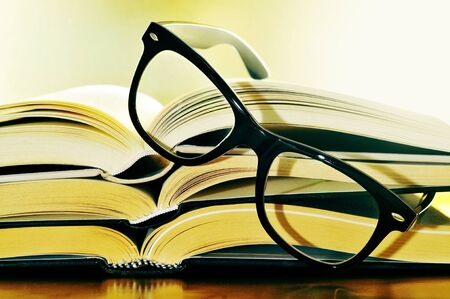 a pile of books and glasses symbolizing the concept of reading habit or studing photo
