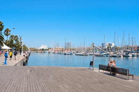 prior: Barcelona, Spain - August 16, 2011: Port Vell from Rambla del Mar in Barcelona, Spain. It was built as part of an urban renewal program prior to the 1992 Barcelona Olympic Games