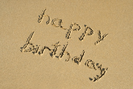 felicitaciones cumpleaÑos: feliz cumpleaños escrito en la arena de una playa Foto de archivo