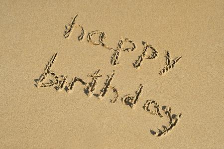 happy holidays: gelukkige verjaardag geschreven op het zand van een strand