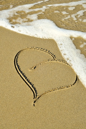 rest in peace: a heart drawn on the sand of a beach