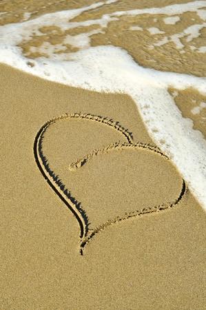 pardon: un coeur dessiné sur le sable d'une plage