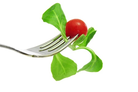 rapunzel: closeup of a fork with corn salad leaves and a cherry tomato