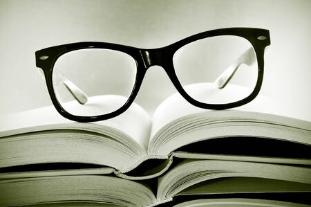 bookworm: a pile of books and glasses symbolizing the concept of reading habit or studing