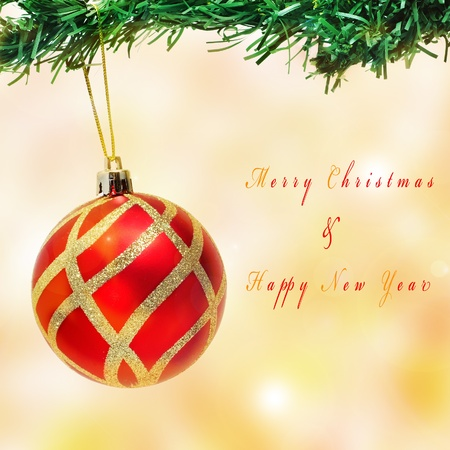 x mas: a christmas ball hanging on a christmas tree and sentence Merry Christmas and Happy New Year Stock Photo