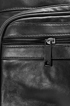 handled: closeup of a black leather travel bag