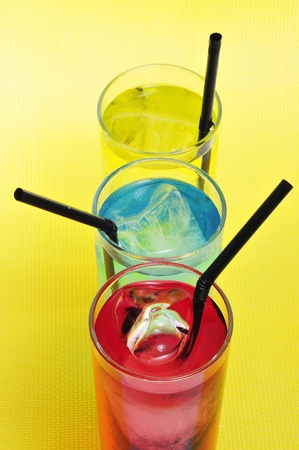 thirstiness: some glasses with cocktails of different colors on a yellow background