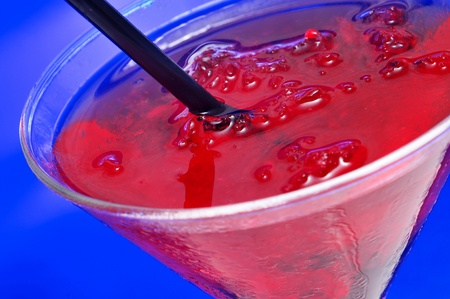closeup of a glass with cocktail on a blue background photo