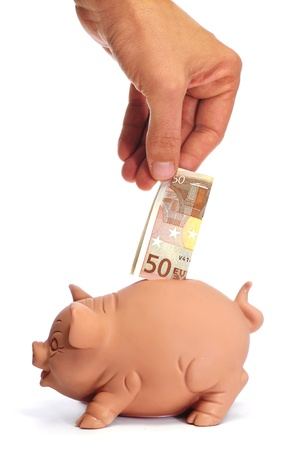 money box: someone inserting a ticket 50 euros in a piggy bank Stock Photo