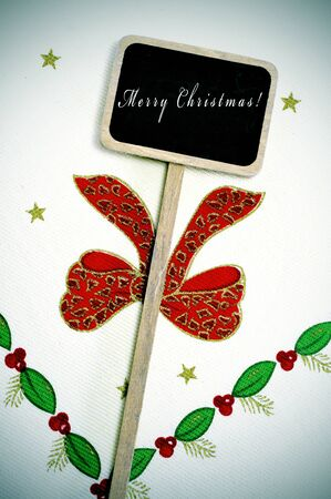 sentence merry christmas written in a chalkboard on a christmas fabric photo