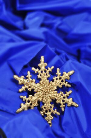 a golden christmas ornament in the shape of a snowflake on a blue fabric background photo