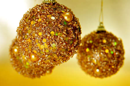 shiny golden christmas balls on a golden background photo