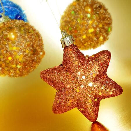some shiny golden christmas ornaments on a golden background photo