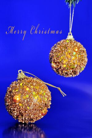 sentence merry christmas and some shiny golden christmas balls on a blue background photo