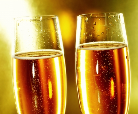 a pair of glasses of champagne on a golden background photo