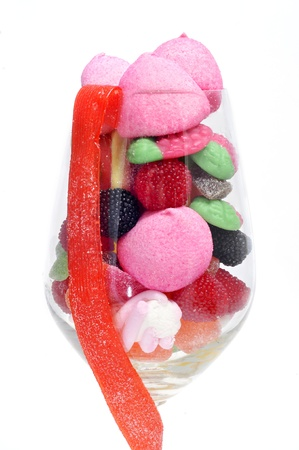 a glass with candies on a white background photo