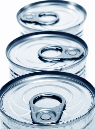 food preservation: closeup of a pile of cans on a white background
