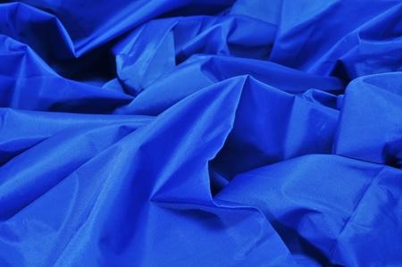 acrylic fiber: closeup of a blue satin fabric backdrop