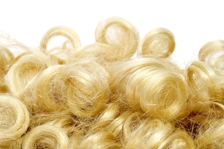 periwig: closeup of a curly blonde wig on a white background