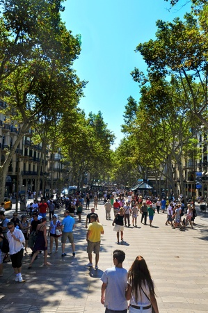 promenade: Barcelona, Spain - August 16, 2011: La Rambla in Barcelona, Spain. Thousands of people walk daily by this popular pedestrian mall 1.2 kilometer-long