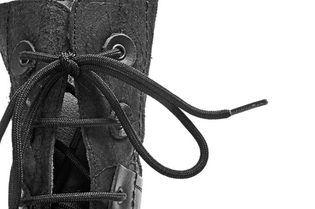 foot gear: closeup of a black leather boot on a white background