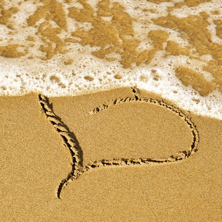 a wave erasing a heart carved on the sand of a beach photo
