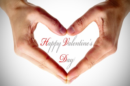man hands forming a heart and the sentence happy valentines day Stock Photo - 11944515