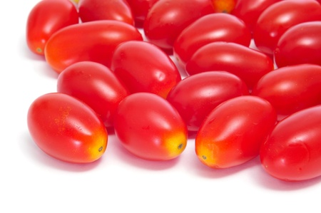a pile of baby plum tomatoes on a white background photo