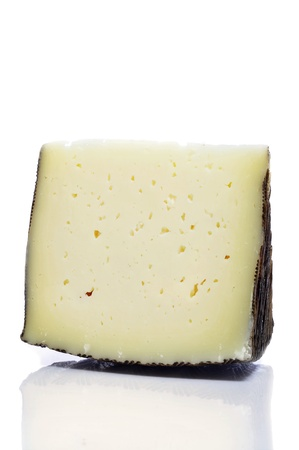cured: a piece of manchego cheese on a white background