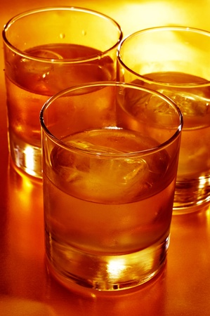 addictive drinking: closeup of some glasses with mixed drinks in a club