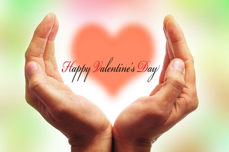 man hands forming a cup and the sentence happy valentines day with a heart in the background Stock Photo - 11996386