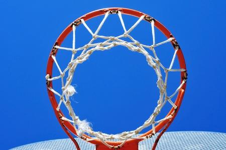 b ball: closeup of an outdoors basketball basket over the blue sky