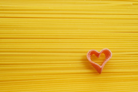 heart shaped pasta on a spaghetti background photo