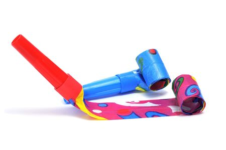 noisemaker: some party horns of different colors on a white background