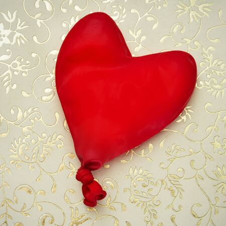 heart-shaped balloon on a golden patterned background photo