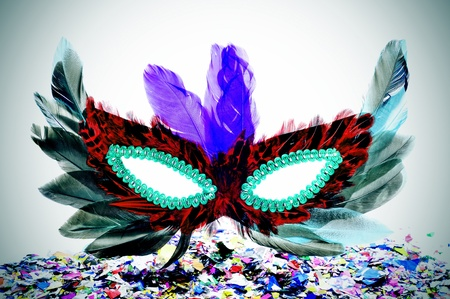 a carnival mask with feathers of different colors and confetti photo