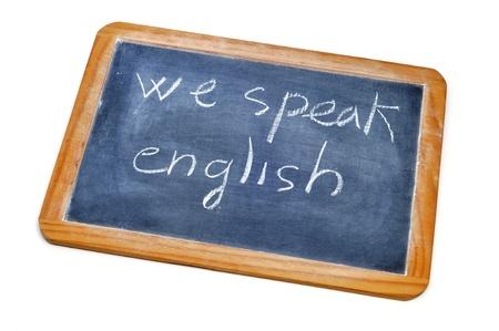 english text: sentence we speak english written with chalk on a blackboard  Stock Photo
