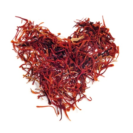 a pile of saffron forming a heart on a white background photo
