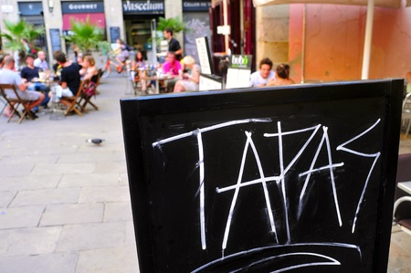 Barcelona, Spain - August 16, 2011: A blackboard with word tapas in a restaurant terrace in Born district in Barcelona, Spain. This district houses a large number of bars and restaurants Stock Photo - 12256226