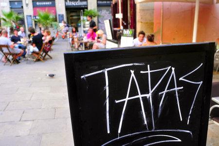 barcelone: Barcelone, Espagne - 16 Août 2011: Un tableau noir avec des tapas de mots dans une terrasse de restaurant dans le quartier Born à Barcelone, Espagne. Ce quartier abrite un grand nombre de bars et de restaurants Éditoriale