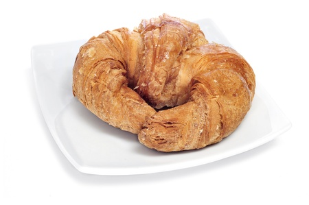 a plate with a croissant on a white background Stock Photo - 12553685