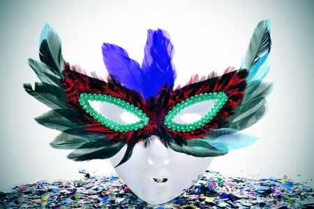 carnivale: a mask with a carnival mask with feathers and confetti of different colors