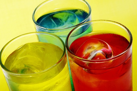 thirstiness: closeup of some glasses with mixed drinks on a yellow background